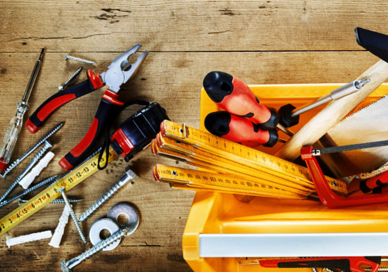 Colorful yellow tool box with assorted DIY hand tools for renovation, woodworking or construction on a rustic wood background