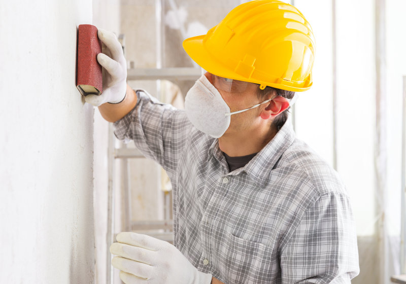 Plasterer or painter sanding the newly plastered surface of a white wall during renovations preparing it for painting in a high key house interior