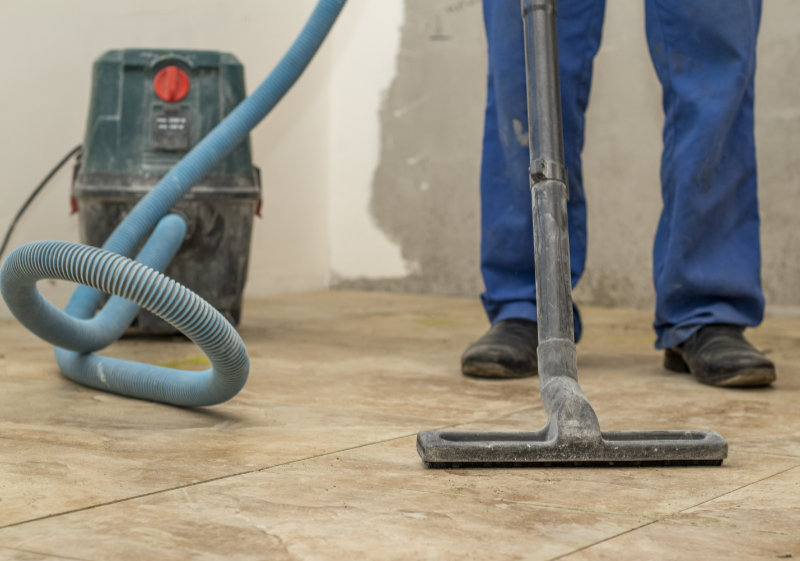 the man vacuums the tile after laying. preparation for jointing.